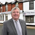 Phil Bates outside his rebranded offices in Neston - low res
